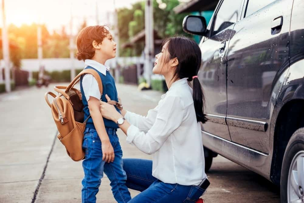 protective mom with young son at drop off for school