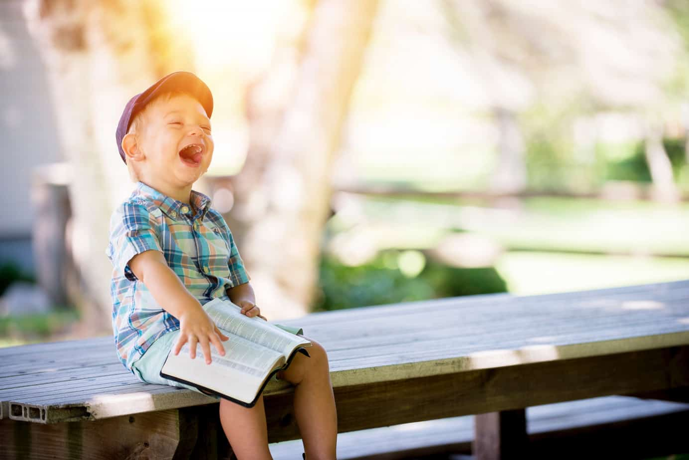 A child laughing at funny jokes for kids.