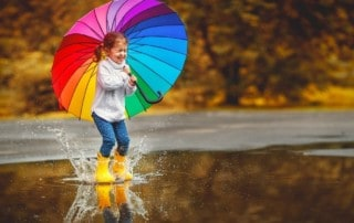 girl with rain boots and umbrella jumping in a puddle