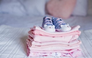 stack of pink baby clothes