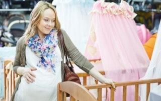 Pregnant woman looking at cribs
