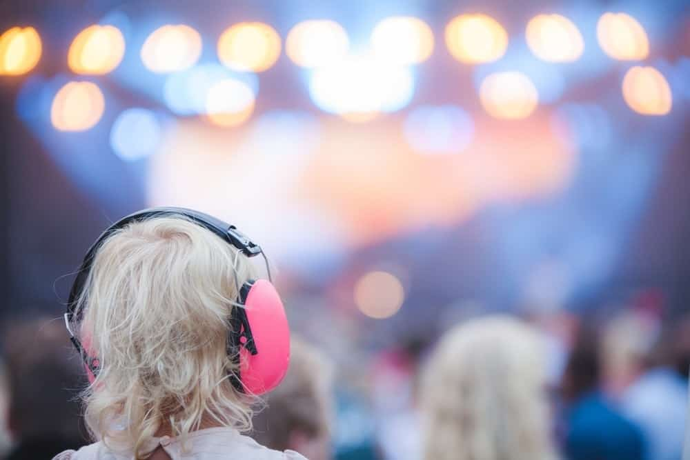 young child wearing earmuffs at outdoor concert