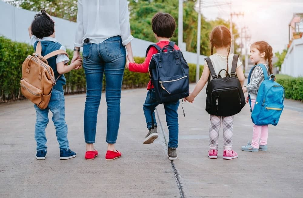mom with four young kids wearing backpacks
