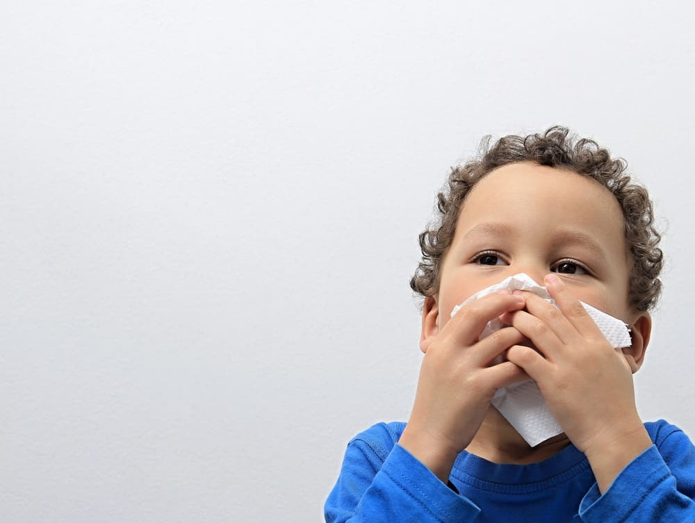 boy blowing nose into tissue