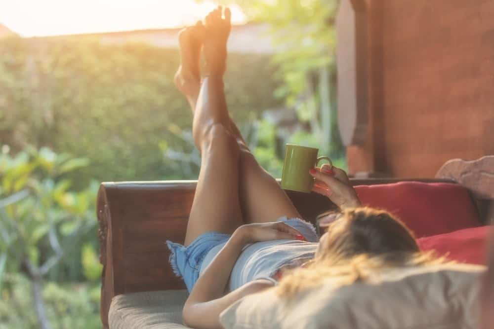 woman relaxing on porch with cup of coffee