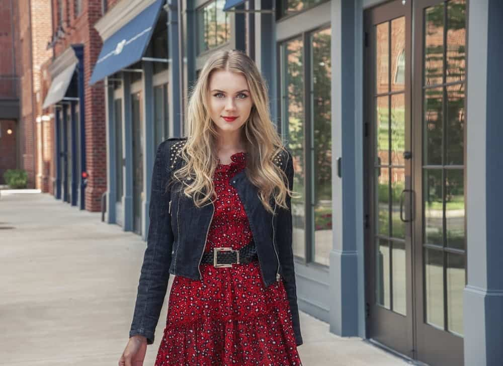 woman outside in red dress and black jacket