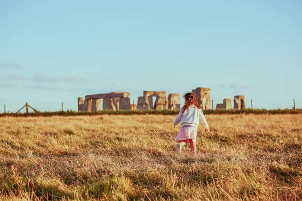 small girl with Stonehenge in background
