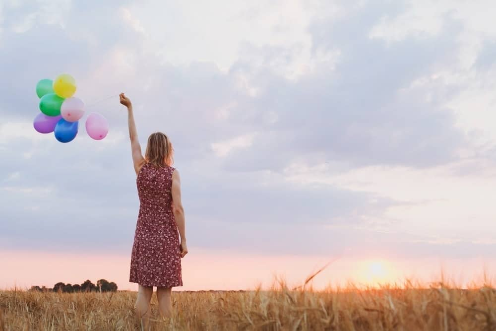 woman letting go of colorful balloons in a field