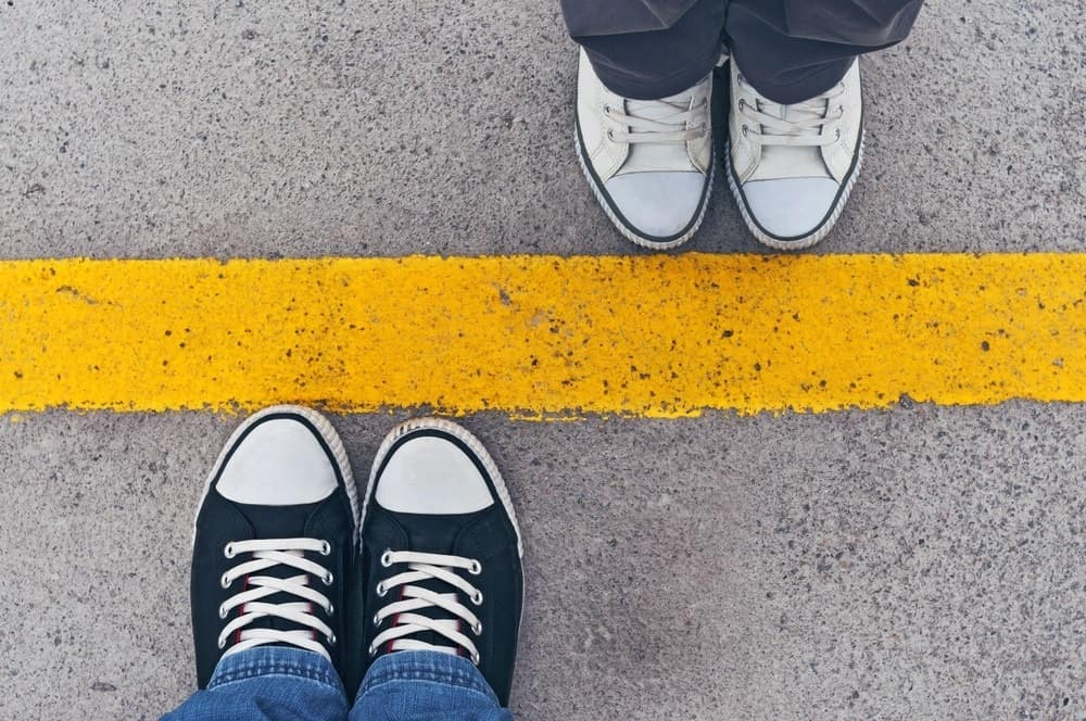 two pairs of shoes on opposite sides of yellow line
