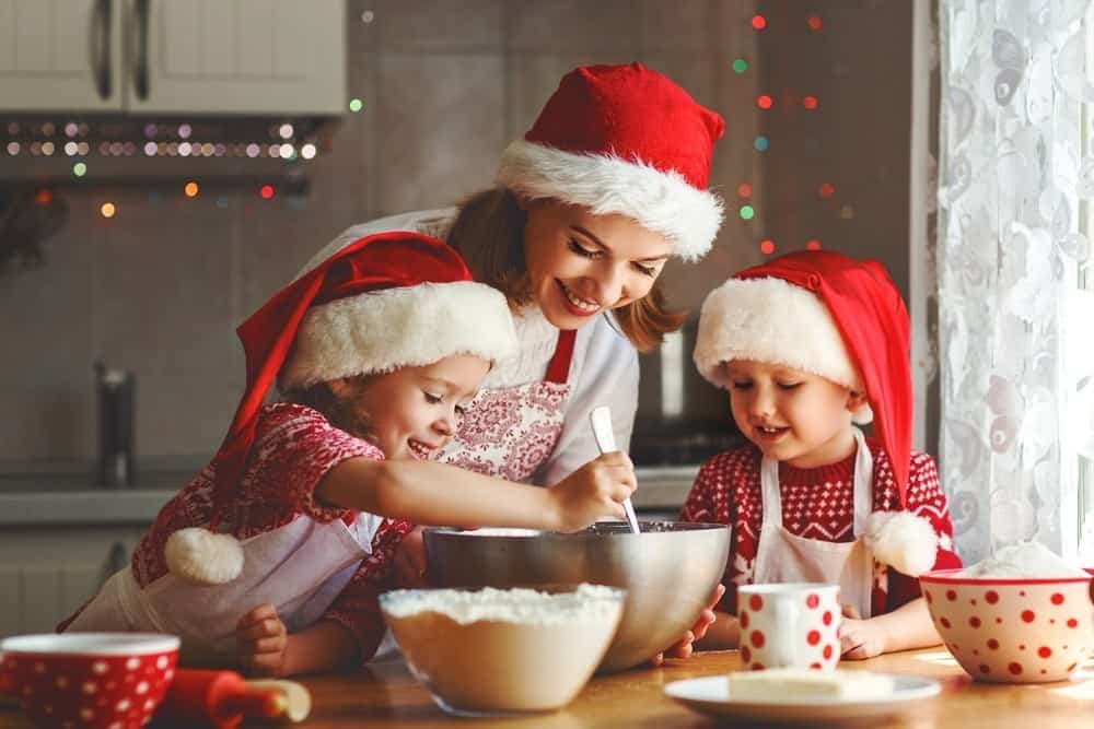 happy mom baking with two young kids