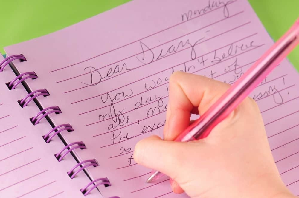 girl writing in pink diary