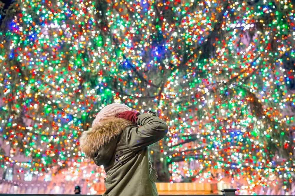 child looking up at Rockefeller Christmas tree in New York City