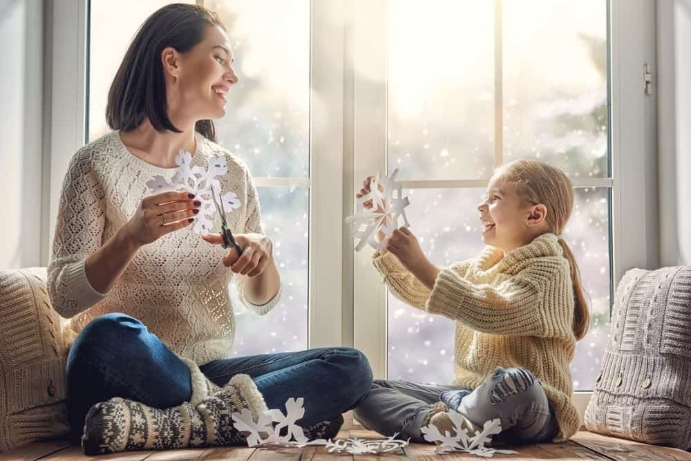mom and daughter cutting paper snowflakes