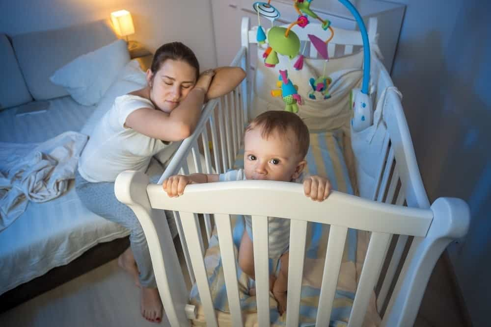 sleeping mom leaning on crib with awake baby