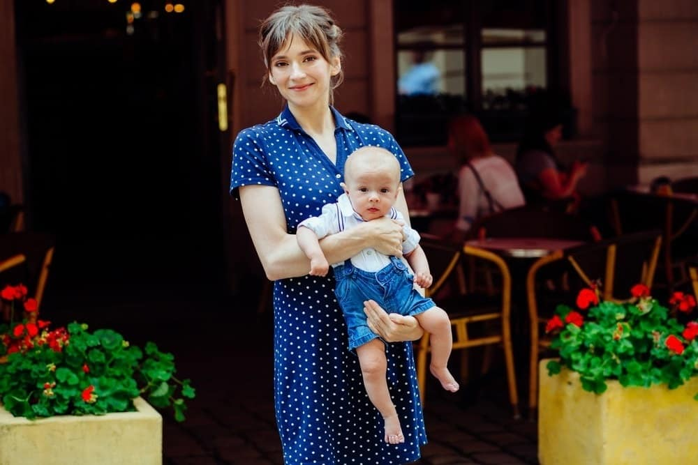 young mom in casual blue dress holding baby boy