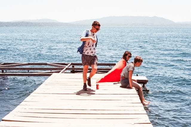 Two boys and a girl wearing a cape sitting on a wooden dock overlooking the water