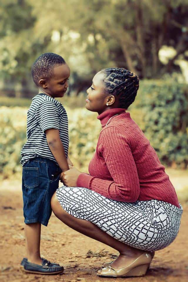 African-american woman in red sweater with white and black skirt kneeling down talking to son in blue jean shorts