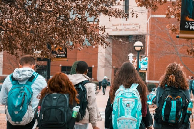 Young adults walking together with booksacks on campus.