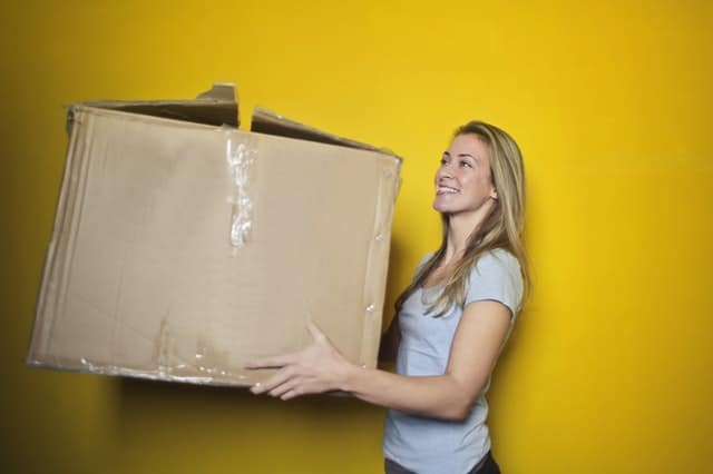 Blonde woman carrying cardboard box in front of yellow wall.