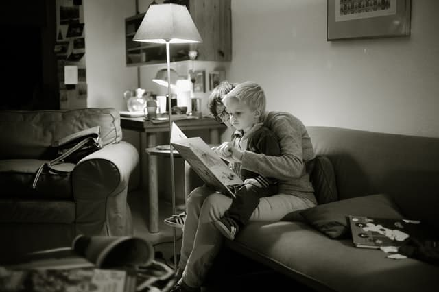 black-and-white photo of woman reading to a blonde toddler boy in her lap