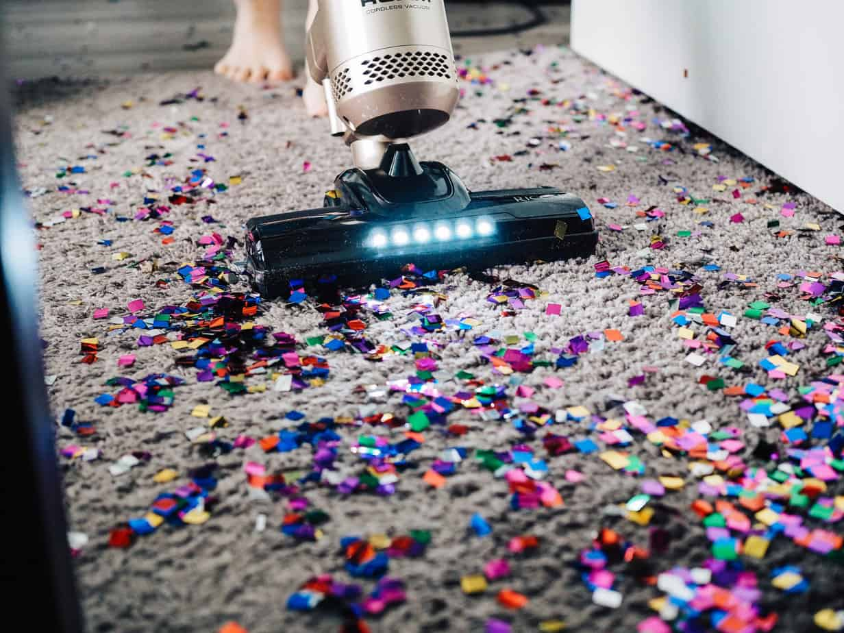 Child vacuuming confetti from carpet