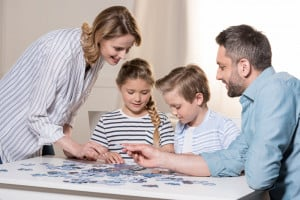 smiling family playing puzzle
