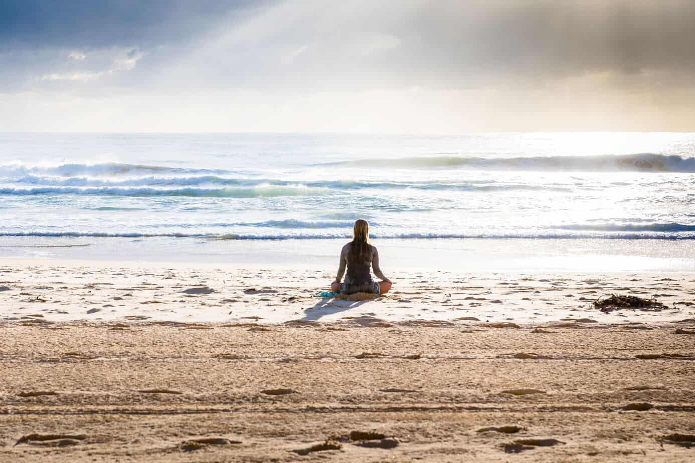 Mother Woman Sitting in Front of Ocean Meditating